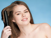 Close up portrait of young woman with hair iron — Stock Photo