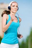 Beautiful woman running in green park — Stock Photo
