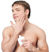 Man putting on cream lotion — Stock Photo