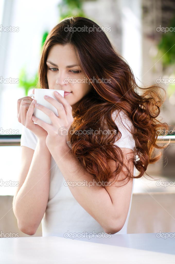 A young attractive woman sitting in a cafe with a coffe — Stock Photo #8582359