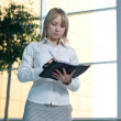 Young businesswoman with day planner in lobby — Stock Photo
