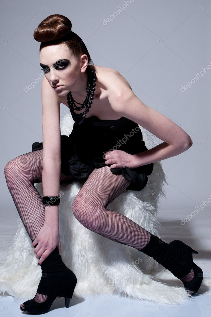 Studio shot of a young, beautiful, fashion model with black make-up, dress and beads — Stock Photo #8604275