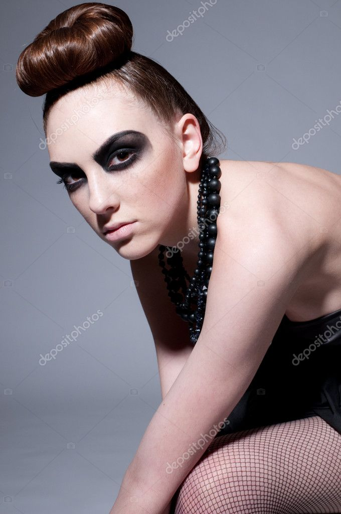 Studio shot of a young, beautiful, fashion model with black make-up, dress and beads — Stock Photo #8604334