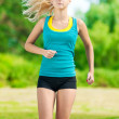 Stock Photo: Young woman running in green park