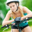 Young smiling woman on bike - Stockfoto