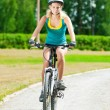 Young smiling woman on bike -  