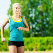 Young woman running in green park — Stockfoto