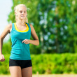 Young woman running in green park — Foto Stock