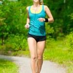 Beautiful young woman running on music — Stock Photo