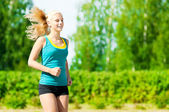 Young woman running in green park — Stock Photo