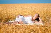 Mooie vrouw poseren in tarweveld. picknick. — Stockfoto