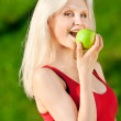 Woman with green apple at park — Stock Photo