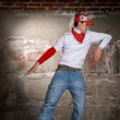 Hip hop boy dancing in modern style over grey brick wall — Stock Photo