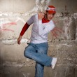 Hip hop boy dancing in modern style over grey brick wall - Stock Photo