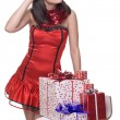 Close up portrait of girl in santa dress with gifts - Stockfoto