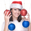 Woman in santa dress and decoration balls — Stock Photo