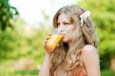Uśmiechnięta kobieta picia soku pomarańczowego — Zdjęcie stockowe