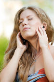 A young girl listening music outdoor — Stock Photo