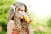 Smiling woman drinking orange juice — Stock Photo