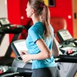 Gym exercising. Run on on a machine. - Stock Photo
