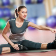 Woman doing stretching fitness exercise at sport gym. Yoga — Photo