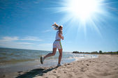 Sport woman running in sea coast — Stock Photo