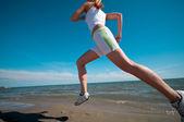 Sport woman running on beach — Stock Photo