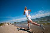 ビーチを走るスポーツ女性 — ストック写真