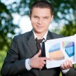 Business man show graph at park. Student — Stock Photo #8650998