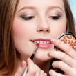 Beautiful young adult woman applying cosmetic lipstick brush — Stock Photo #8655097