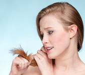 Close up portrait of young displeasure woman with hair ends — Stock Photo