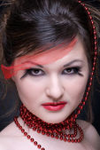 Close up portrait of girl with red lips and beads on black — Stock Photo