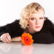 Blond curly woman with a flower in her hands — Stock Photo
