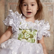 Little girl in white dress with a tiara on her head - Stock Photo