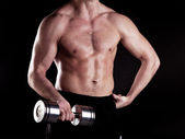 Muscular powerful man lifting metal weights — Stock Photo