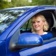 Blonde woman sitting behind the wheel of a car — Stock Photo #8906676
