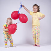 Two cute girls in pink pajamas playing with red balloons — Stock Photo