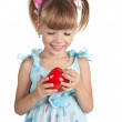 A little sweet girl with a red pepper in her hand - Stock Photo