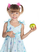 Pretty girl in a blue dress with an apple in her hand — Stock Photo