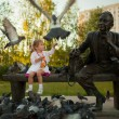 A little girl feeding the pigeons in the park near the statue — Stock Photo #9196824