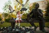 A little girl feeding the pigeons in the park near the statue — Stock Photo