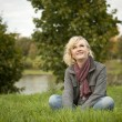 Blonde sits on the grass — Stock Photo #9445809