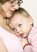 Baby girl cuddling up to her mother — Stock Photo