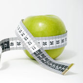 Fresh green apple with measuring tape — Stock Photo
