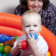 Baby playing with colorful balls - Stock Photo