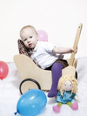 Baby climbing into dolls pram — Stock Photo