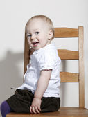 Proud happy baby girl sitting on chair — Stock Photo