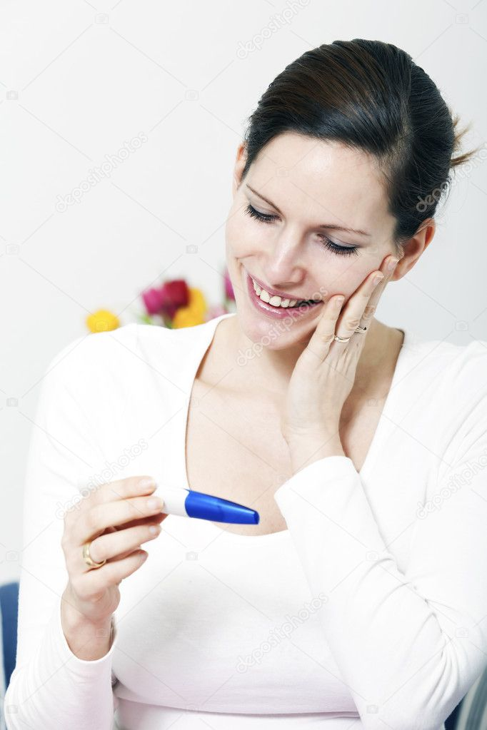 Beautiful happy woman holding a positive pregnancy test kit in her hands and smiling — Stock Photo #9581174