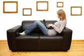 Mladá žena leží na pohovce a s notebookem — Stock fotografie