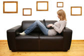 Young woman lying on a sofa and using a laptop — Stock Photo